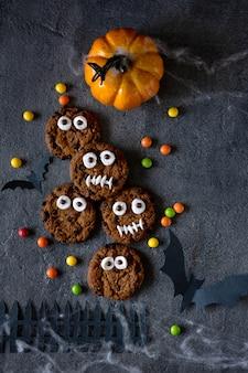 할로윈 쿠키. 테이블에 초콜릿 비스킷으로 만든 재미 있은 괴물. 할로윈 파티 장식. 속임수 또는 치료 개념.