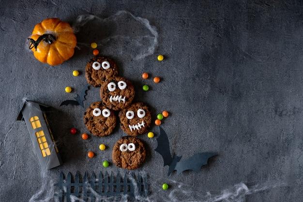 Печенье на хэллоуин. забавные монстры из печенья с шоколадом на столе. украшение вечеринки в честь хэллоуина. кошелек или жизнь концепция.