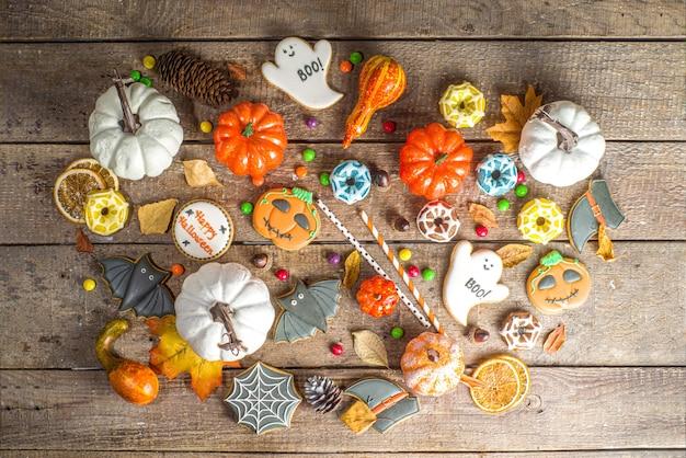 ハロウィーンのクッキー、お菓子、装飾の背景。トリックオアトリートのコンセプト。伝統的なハロウィーンのジンジャーブレッド、カボチャと木製の背景の上の装飾とキャンディー上面図コピースペース