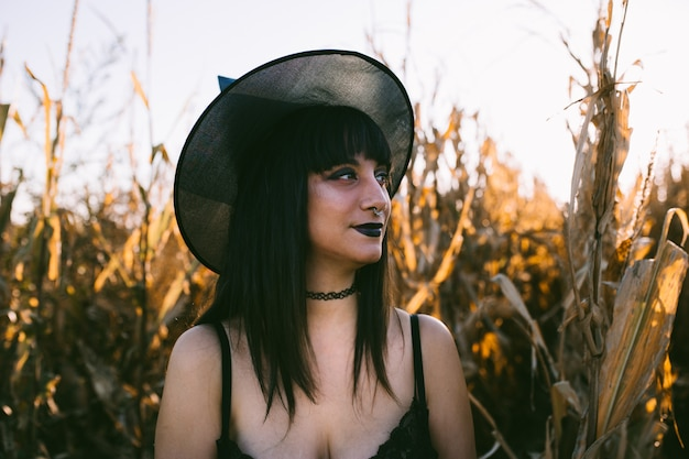 Halloween costume witch girl portrait in a cornfield at sunset. beautiful serious young woman in witches hat with long black hair and dark lips.