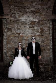 Пара хэллоуина. одетые в свадебную одежду романтическая пара зомби.