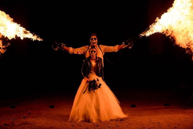 火炎放射器と一緒に立っているハロウィーンのカップル。