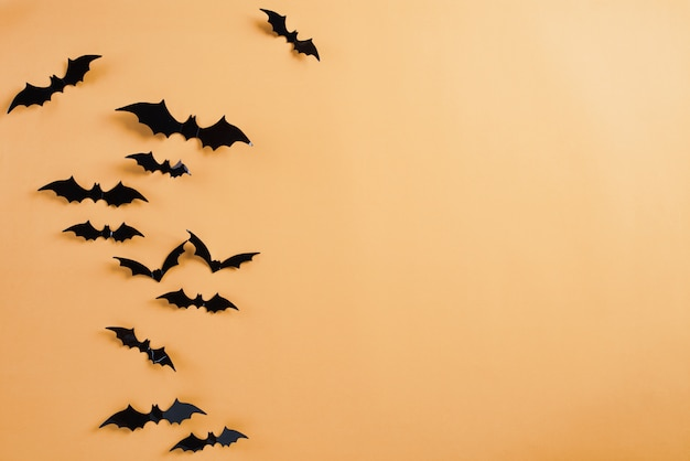 Halloween crafts, black paper bats flying over orange background