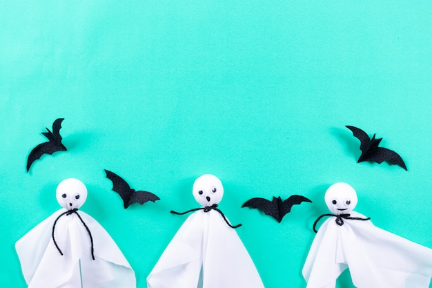 Halloween crafts, ghost and bats on pastel green paper background.