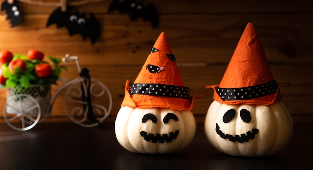 Halloween crafts, white pumpkin wearing witch hat with bat on wooden table background