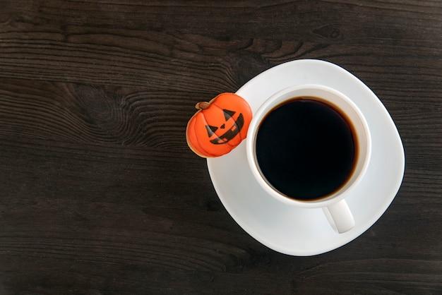 ブラックコーヒーのハロウィーンカップがテーブルの上にあります。カボチャの形をしたオレンジ色のクッキーが白い受け皿の上にあります。コピースペース