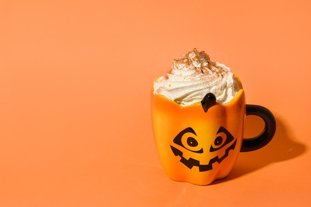 Halloween cup of pumpkins coffee latte with whipped cream on orange background.