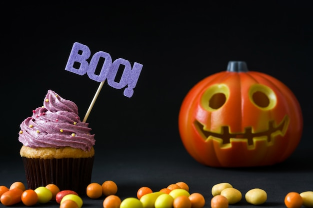 Halloween cupcake with pumpkin on black