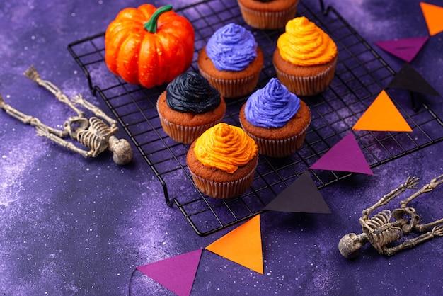 Кексы на хэллоуин с черным, фиолетовым и оранжевым кремом и декором