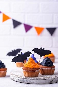 黒、紫、オレンジ色のクリーム色と装飾が施されたハロウィーンのカップケーキ