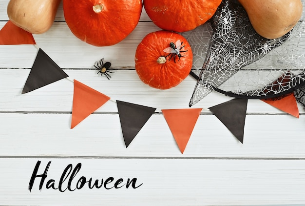 Halloween day ripe pumpkins and halloween paraphernalia a witchs hat flags spiders are lying