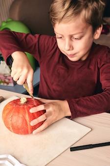 ハロウィーン、装飾、休日のアイデア-ナイフ彫刻カボチャまたはジャック・オー・ランタンで子供のクローズアップ。 6歳の男の子は家庭で楽しい活動をしています。息子と一緒に時間を過ごすお母さん