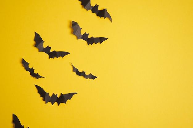 Концепция украшения хэллоуина черная бумага летучие мыши желтая картонная поверхность с копией пространства для тетекст