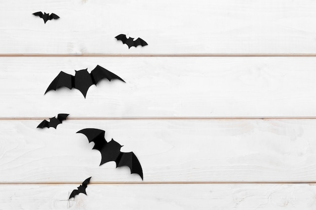 Halloween and decoration concept - paper bats flying on wooden copyspace