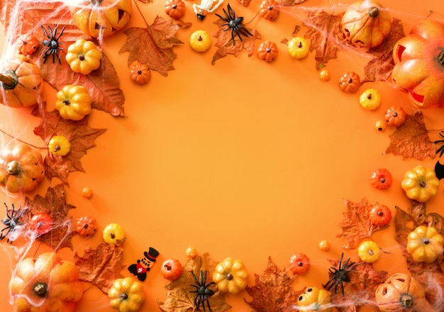 Halloween decoration on orange color frame background top view with copy space