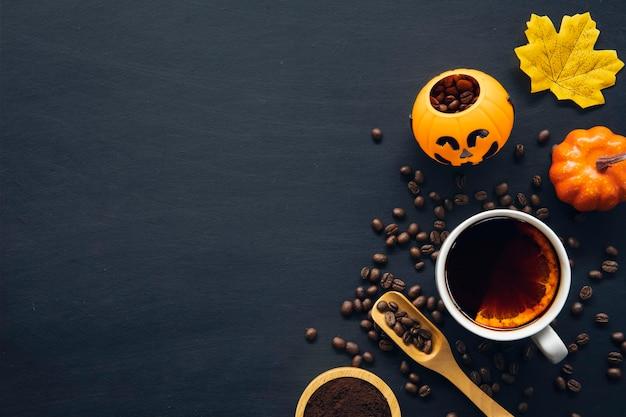 Украшение на хэллоуин с горячим кофе и зернами на темном фоне