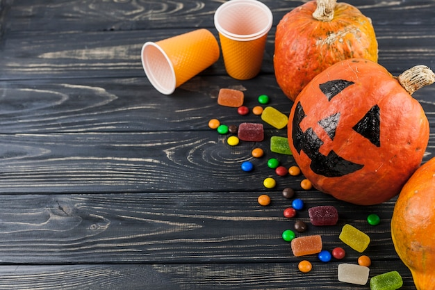 Halloween decorations and candies on wooden floor