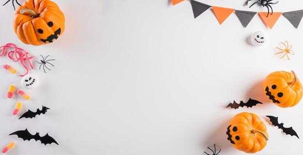 파스텔 오렌지 배경에 호박, 종이 박쥐, 검은 거미로 만든 할로윈 장식. 평평한 위치, 텍스트 복사 공간이 있는 위쪽 보기.