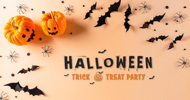 Украшения хэллоуина из тыквы, бумажных летучих мышей и черного паука на пастельно-оранжевом фоне. плоская планировка, вид сверху с текстом на хэллоуин