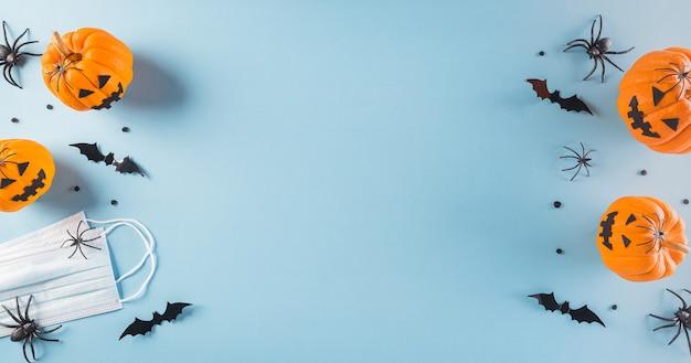호박, 종이 박쥐 및 파스텔 블루 배경에 외과 얼굴 마스크에서 만든 할로윈 장식. covid-19 대유행 상황에서 할로윈 축하의 평면 위치, 평면도.