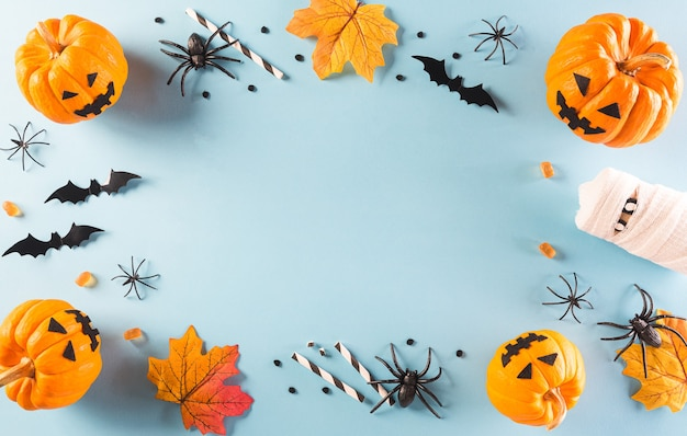 Halloween decorations made from pumpkin, paper bats and black spider on pastel blue background. flat lay, top view with copy space for text.
