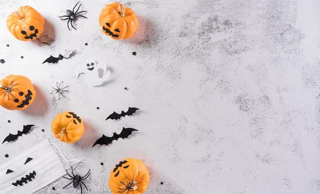 カボチャの紙コウモリの医療用マスクとクロガケジグモから作られたハロウィーンの装飾