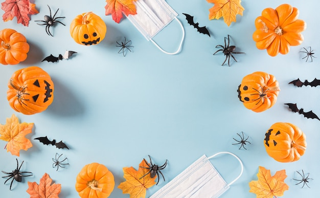 Halloween decorations made from pumpkin, paper bats and surgical face mask on pastel blue background. flat lay, top view of halloween celebration during covid-19 pandemic situation.
