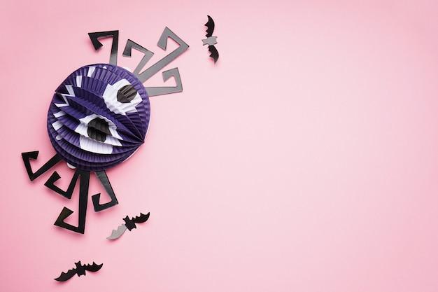 ハロウィーンの装飾、ピンクの背景に紙のクモとコウモリ、テキスト用のスペース、フラットレイ。