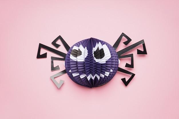 ハロウィーンの装飾、ピンクの背景に紙のクモ。フラットレイ。