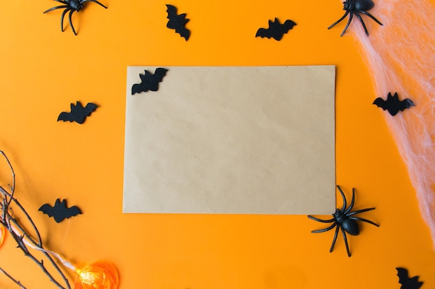 Halloween decorations, pumpkins, bats, web, bugs on orange background. halloween party greeting card with copy space. flat lay, top view.