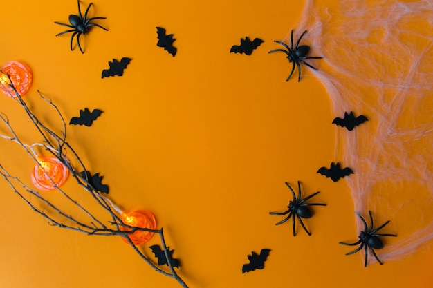 Halloween decorations with pumpkins, bats, web, bugs on orange background. party greeting card with copy space.