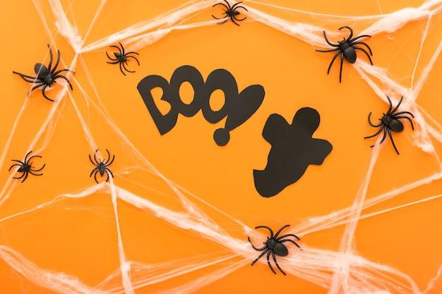 오렌지 배경에 할로윈의 상징으로 거미, 웹, 유령 및 거미와 할로윈 장식. 해피 할로윈 개념입니다.