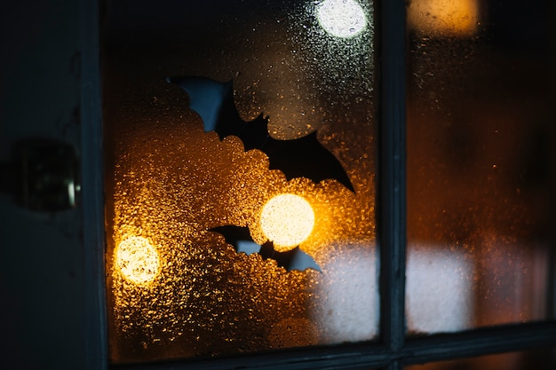 Halloween decorative bats stuck on window with raindrops