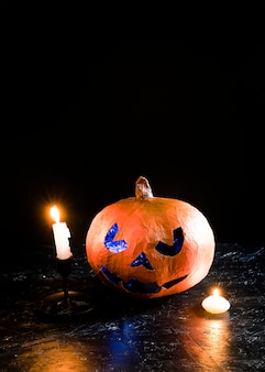 Halloween decorative pumpkin lying among burning candles on sides