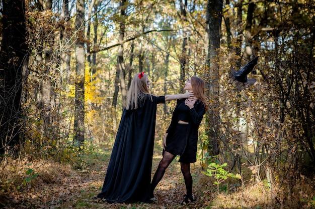 森の中でハロウィーンの悪魔と魔女