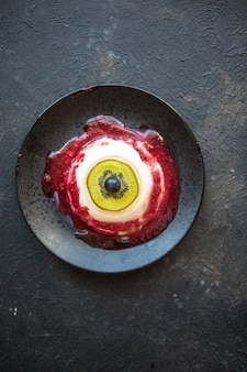 Halloween dessert bloody eye from vanilla panna cotta and kiwi with berry syrup