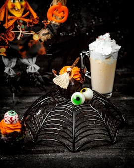 Halloween dessert in a shape of spider web and eyes, and a chocolate brownie