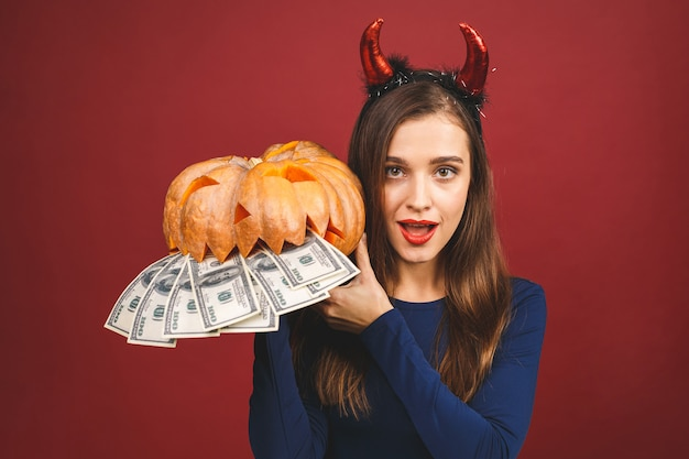 切り分けられたカボチャとお金-赤の背景に分離されたハロウィーンの悪魔。ハロウィーンの衣装の感情的な若い女性。