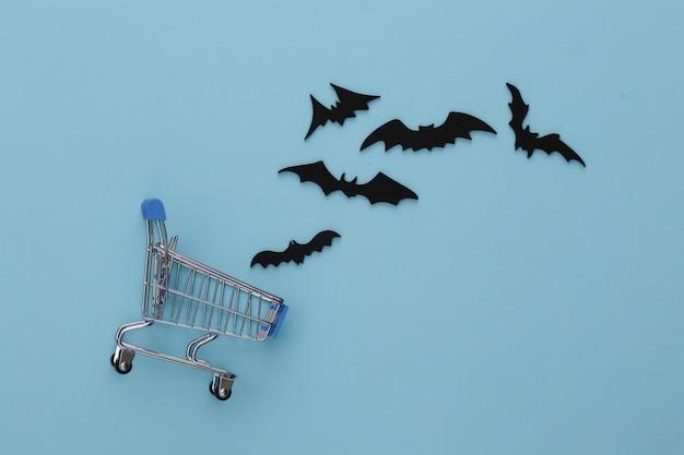 ハロウィーンの割引、ショッピング。スーパーマーケットのトロリーと青の空飛ぶコウモリ。ハロウィーンの装飾