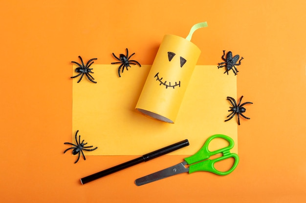 Halloween diy and kids creativity. step by step instruction: making orange monster pumpkin from toilet roll tube. step2 finished work. children craft. eco-friendly reuse recycle.