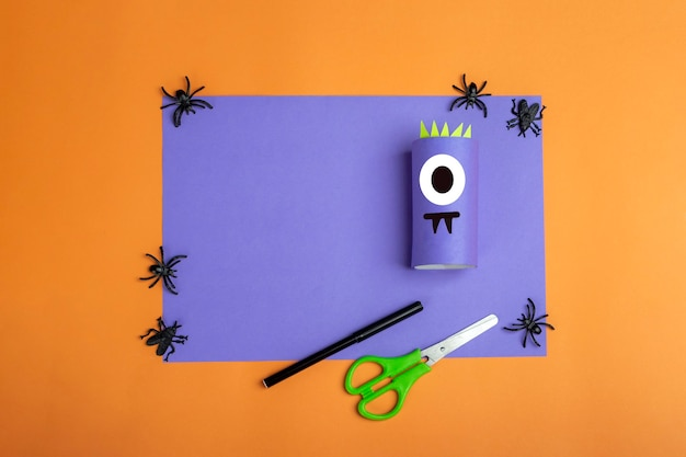 Halloween diy and kids creativity. step by step instruction: making purple monster from toilet roll tube. step2 finished work. children craft. eco-friendly reuse recycle.