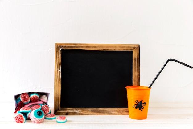 Halloween drink and candies near chalkboard