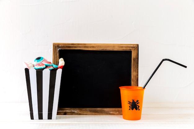Halloween drink and sweets lying near blackboard