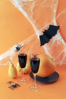 할로윈은 오렌지 배경에 적포도주 호박 거미와 거미줄을 마신다
