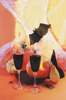 할로윈은 밝은 오렌지색 배경에 와인 호박 거미와 신비로운 장식을 마신다
