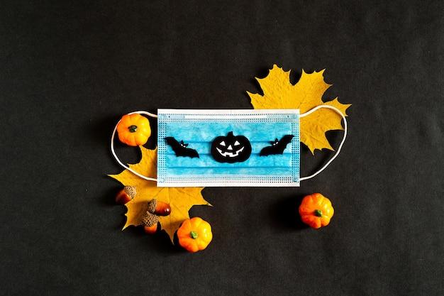 Хэллоуин во время пандемии с желтыми листьями и медицинской маской