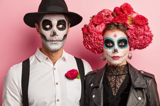 Halloween face art. woman and man stand together in mexican outfit