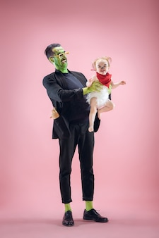 할로윈 가족. 할로윈 의상과 메이크업에 행복 한 아버지와 어린이 신생아 소녀. 블러디 테마: 핑크 스튜디오 배경의 미친 미치광이
