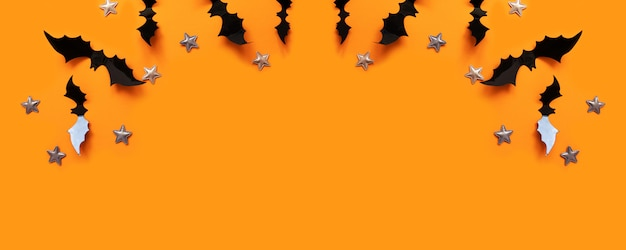 Halloween flat lay composition of black paper bats fly up and gold stars