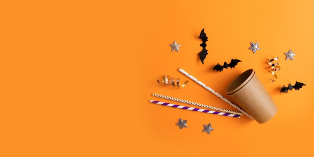 Halloween flat lay composition of paper glasses, multicolored tubules for drinks, black paper bats, stars